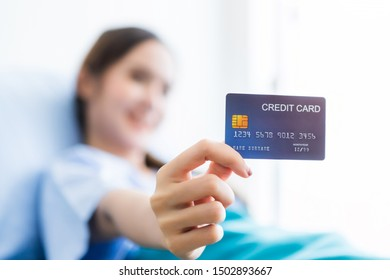 Asian young female patient smiley face Abstract blur with focus on show holding a credit card lying on bed in the room hospital background,payment medical treatment concept