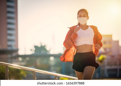 Asian Young fitness sport woman running  and she wears a  mask for protective Dust and pollution on city