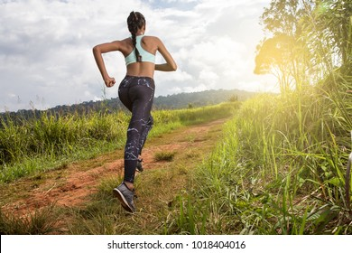 Asian young fitness woman running at forest trail.