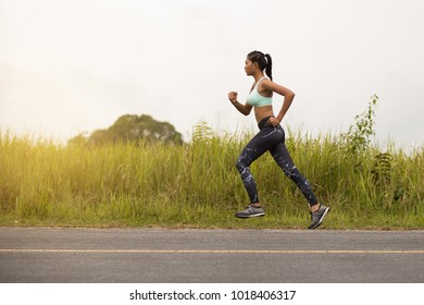 Asian young fitness woman running at forest road.