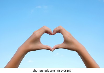 Asian young girl hands in the form of heart on clear blue sky background for Happy valentines day or wedding concept and copy space.