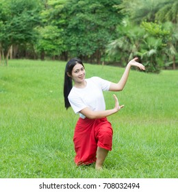 Asian young girl learning Thai dance. Classical Dance in white shirt red loincloth, Demonstrate dance in the garden