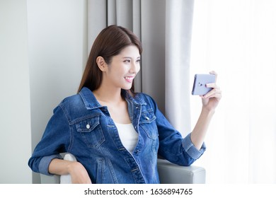 Asian young girl use a smartphone to watch video indoors