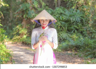 Asian young girl in vietname traditional standing holding red roses in the garden.