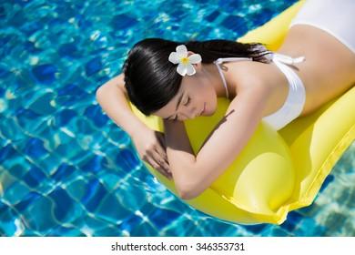 Asian young girl wear bikini swim at the resort. she was sleeping on a rubber raft floating.