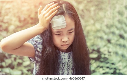 Asian young girl with wound on head cover by plaster
