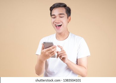 Asian young handsome and cheerful male student with hand gesture and face expression in red shirt with beige color background, suitable for discount promotion