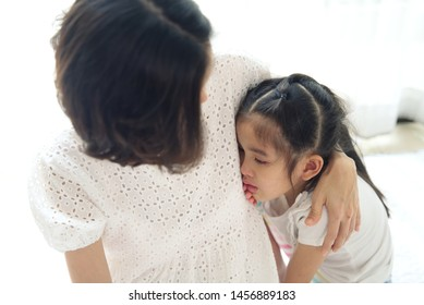 Asian young little girl is crying next to her parent and her mother consoling by touching on head gently. The kid is feeling sad or regret and need mom comforting her. Family relationship concept.