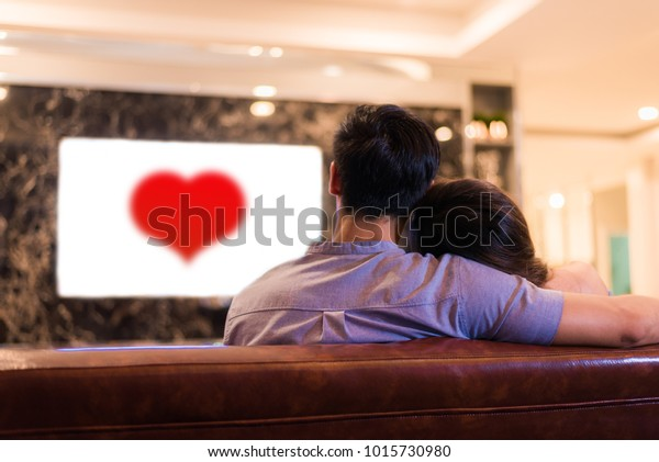 Asian young lovers watching television on sofa. Couples and Relax concept. Holiday and vacation concept. Night dating and honeymoon theme. Back view. Red heart in white screen television