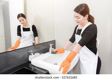 Asian young maid cleaning sink in bathroom, face reflected in the wall mirror, Cleaning service concept