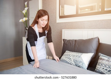 Asian young maid tidying up bed in hotel room, Cleaning service concept