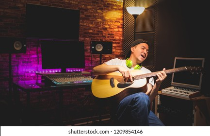 asian young male artist enjoy singing and playing acoustic guitar in home recording studio