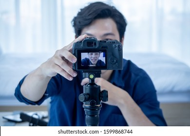 Asian young man blogger setting up camera to present and review product video broadcast live stream video to a social network. blogging, video blog, vlogging, online shopping, and social media concept