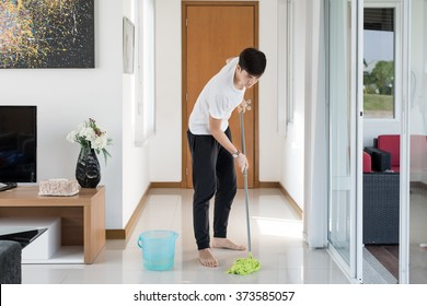 Asian young man cleaning floor at home.