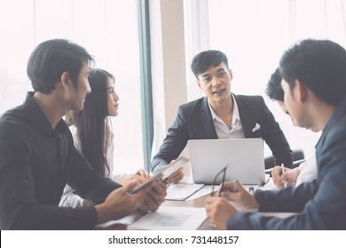 Asian Young man discussing market research with colleagues in a meeting. Business Team of young professionals having a meeting in conference room looking at documents. agreement and hiring concept