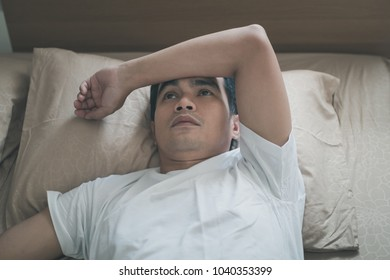 Asian young man drifted and worried while lying on his bed