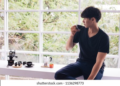 Asian young man drinking coffee inside home