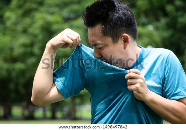 Un jeune homme asiatique se sent mal, sentant quelque chose pue, reniflant son aisselle ou transpirant beaucoup à cause du temps chaud ou après un exercice dans un parc extérieur, expression du visage masculin, concept d'utilisation du déodorant