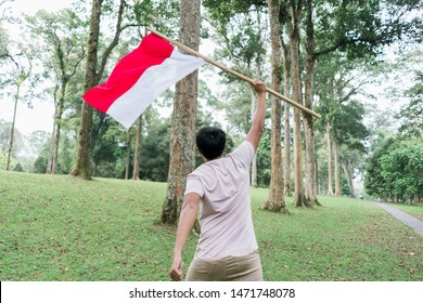 asian young man flapping Indonesian flag with spirit in the park