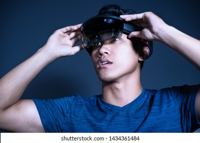 The Asian young man with glasses of virtual reality. Experience VR hololens headset in studio with advanced technology. Surprise face testing new device.