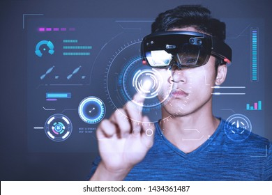 The Asian young man with glasses of virtual reality. Experience VR hololens headset in studio with advanced technology.