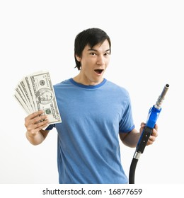 Asian young man with happy expression holding money and gas pump nozzle.