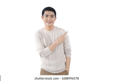 Asian young man in knitted sweater over gray background