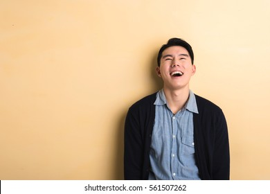 Asian young man laughing in the studio yellow background