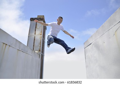 Asian young man making a giant leap in between buildings