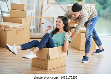 Asian young man playing with his girlfriend while she sitting in big cardboard box they having fun at home