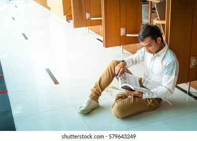 asian young man reading a book while he sitting at pathway