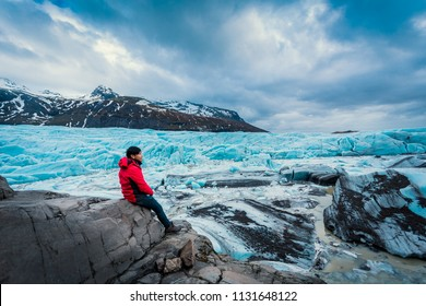 Asian young man in red jacket looking the glacier  in iceland