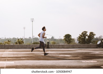 Asian Young man running in the nature. Healthy lifestyle ,side view
