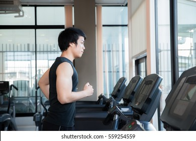 Asian young man running on treadmill in gym. Health and sport concept.
