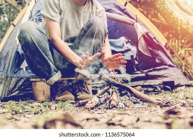 Asian young man sitting in the fire outside the tent, lonely camp in the forest.