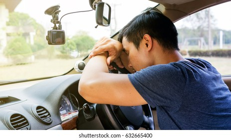 Asian young man sleeping in his car.