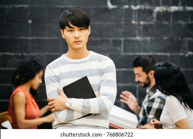 Asian young man with tablet posing unemotionally at camera in office with communicating colleagues.