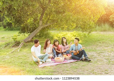 Asian young man take a picnic with his friends at the park