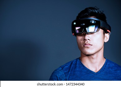 The Asian young man with virtual reality glasses. Experience VR hololens headset in studio with advanced technology.