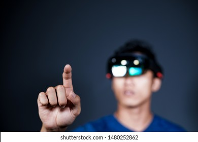 The Asian young man with virtual reality glasses experiences VR hololens headset in studio with advanced technology.