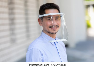 Asian young man wearing face shield for healthcare which is required for doctor and general public to prevent COVID-19.
