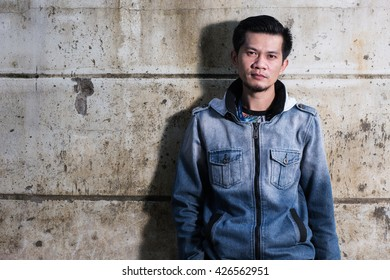 Asian young man wearing jeans clothes stand on the ground in front of the cracked ruined wall.