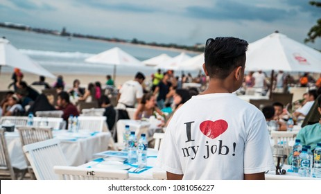 """Asian young man wearing T-shirt """"I love my job"""" while working on the beach in holiday"""