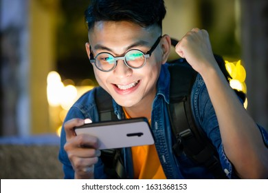asian young man win mobile games on smart phone with fist gesture outdoor in the evening