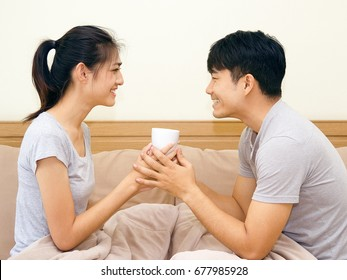 Asian young man and woman holding coffee cup on the bed. The lover smile and look at each other face happily.