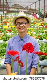 Asian young man working at flower plantation in spring time.