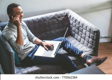 Asian young man working at home with smartphone and laptop on sofa.