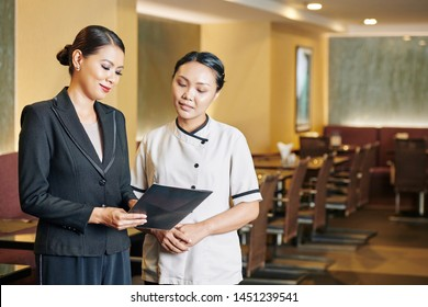 Asian young manager in formalwear standing and examining the menu together with Asian waitress in white uniform at the restaurant