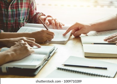 Asian young man,Homosexuality or woman sitting pointing studying examining. Tutor books with friends. Young students campus helps friend catching up and learning. People, learning, education