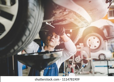 Asian young mechanic working under car at the garage. mechanic oil change service